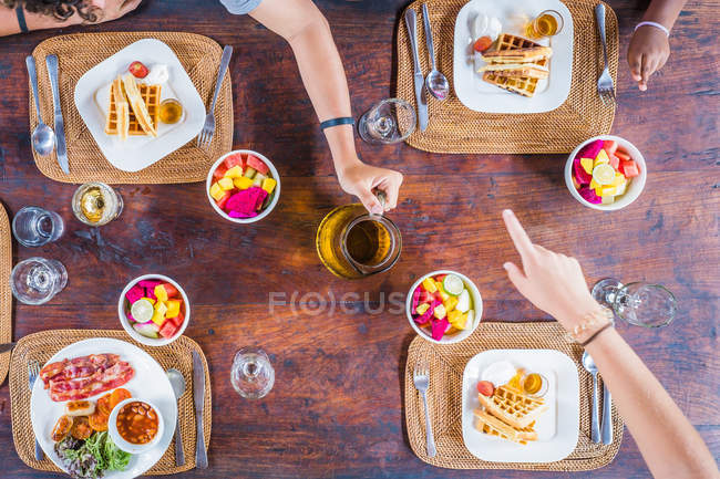 Three children eating breakfast, top view — стокове фото