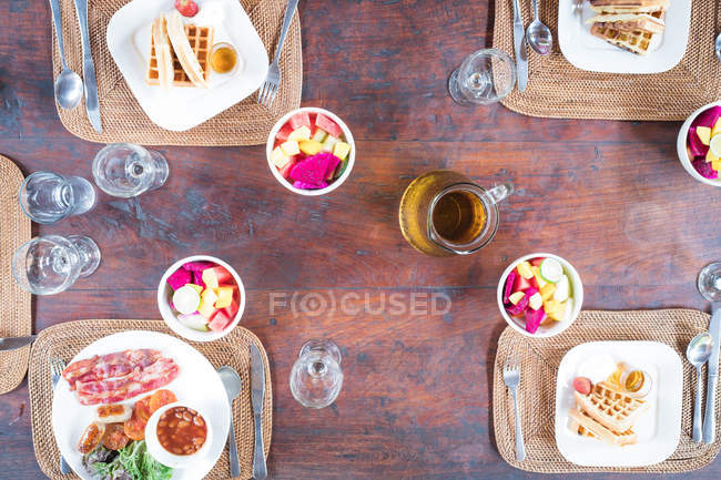 Overhead view of breakfast over wooden table — Stock Photo