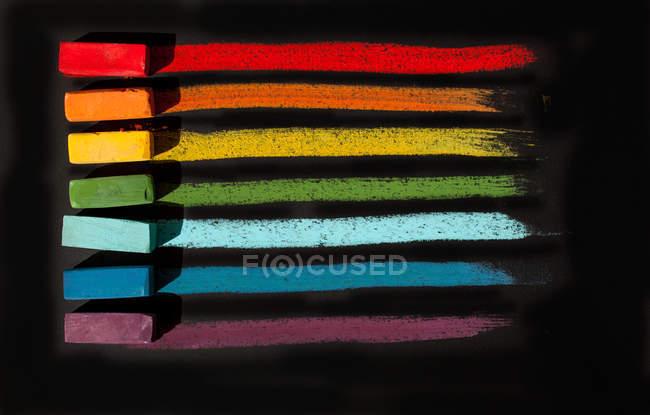 Pasteles al óleo suaves multicolores en fila sobre fondo negro - foto de stock