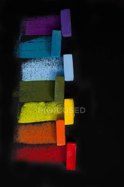 Multi-colored soft oil pastels in a row on black background — Stock Photo