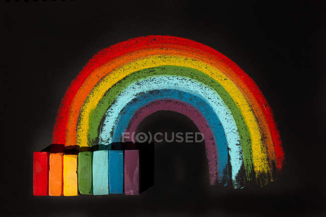 Multi-colored soft oil pastels and a rainbow drawing — Stock Photo