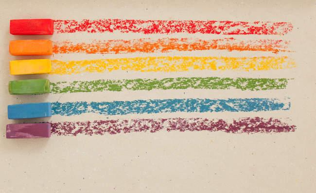 Разноцветные мягкие масляные пастели подряд на белом фоне — стоковое фото