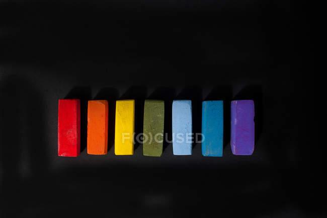 Pastels à l'huile douce multicolores dans une rangée sur fond noir — Photo de stock