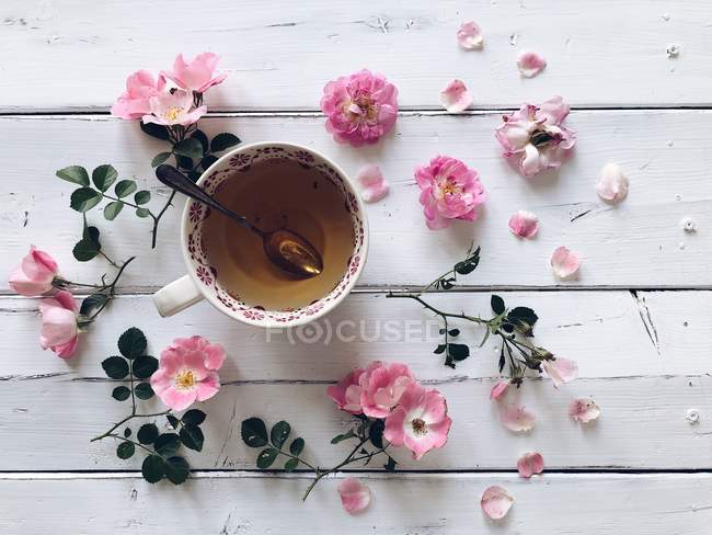 Top view of Cup of tea and pink roses — Stock Photo