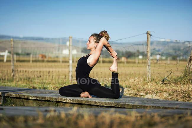 Woman on Los Lances beach doing a king pigeon yoga pose, The Strait Natural Park, Tarifa, Cadiz, Andalusia, Spain — стоковое фото