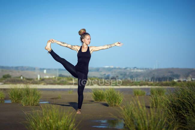 Женщина на пляже los lances делая рука к носу представления yoga, пролив природный парк, tarifa, cadiz, andalusia, Испания — стоковое фото