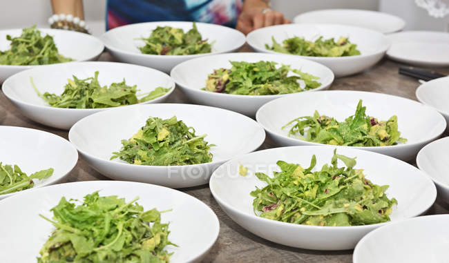 Mulher preparando pratos de salada de abacate com molho de iogurte — Fotografia de Stock