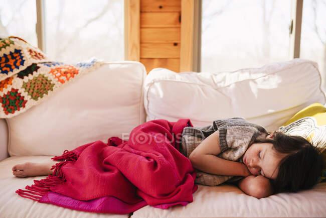 Chica durmiendo en un sofá - foto de stock