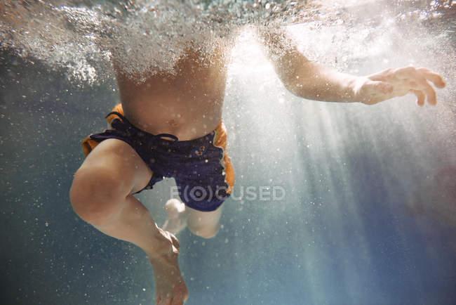 Крупный план мальчика, плавающего под водой в бассейне — стоковое фото