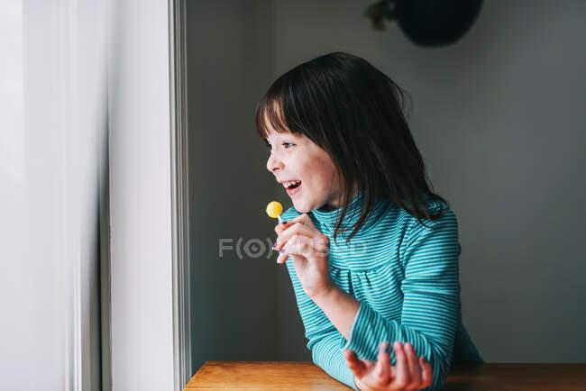 Портрет улыбающейся девушки с леденцом — стоковое фото