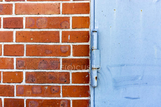 Closeup view of blue metal door and brick wall — Stock Photo
