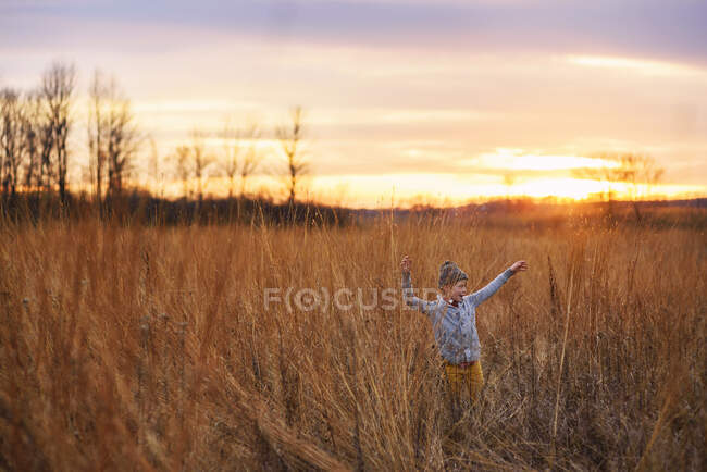 Boy standing in a field with his arms in the air, United States — Stock Photo