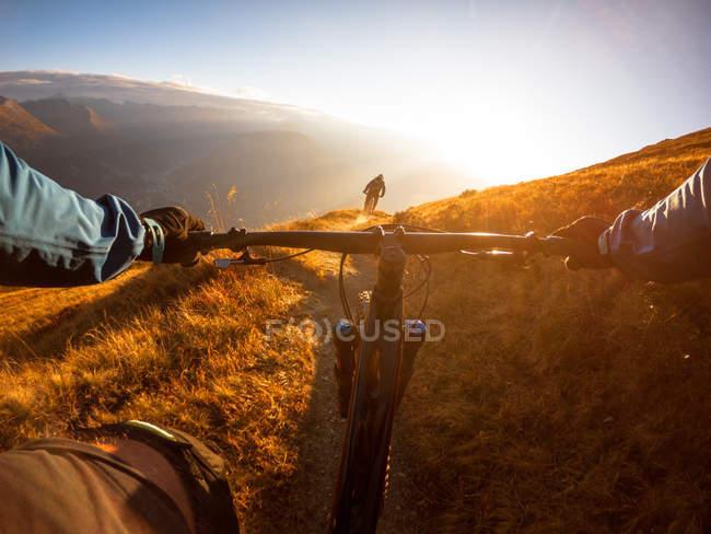 Личная перспектива человека на горном велосипеде с другом в Альпах, Гаштайн, Зальцбург, Австрия — стоковое фото