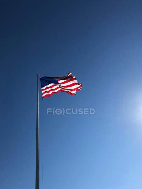 American flag blowing against a blue sky, United States — Stock Photo