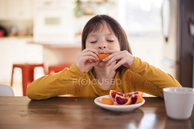 Girl sitting at a table eating a blood orange — Stock Photo