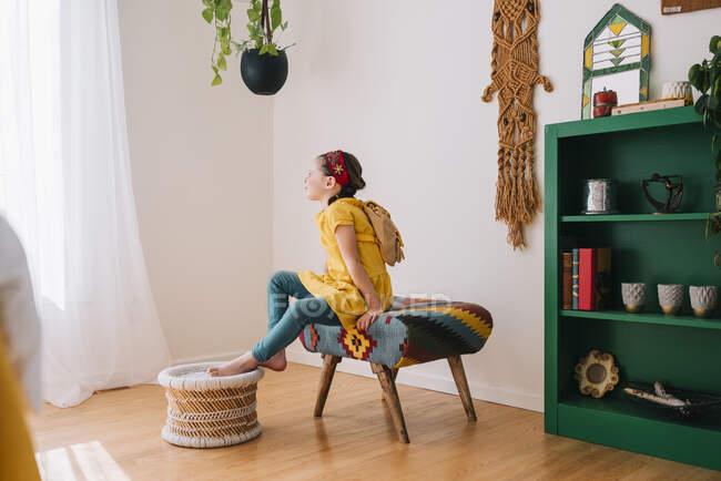 Девушка сидит на стуле и смотрит в окно. — стоковое фото