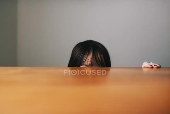 Девушка прячется за столом, обрезанный образ — стоковое фото