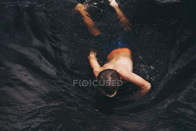 Vista aérea de un niño nadando en un lago, Estados Unidos - foto de stock
