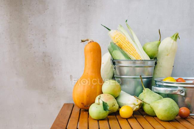 Свежесобранные фрукты и овощи на деревянном столе — стоковое фото