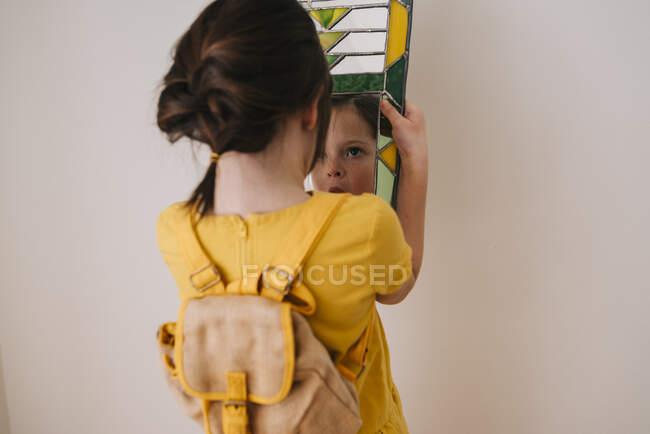 Vista trasera de una chica mirando su reflejo en un espejo - foto de stock