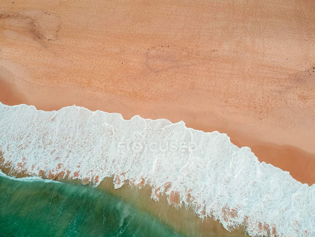 Aerial view of foamy wave crashing at beach — Stock Photo