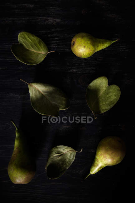 Pears arranged on leaves over black table — Photo de stock