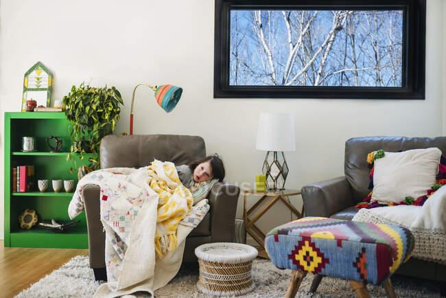 Девушка свернулась калачиком на кресле с одеялом, покрывающим ее — стоковое фото