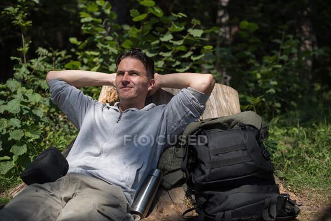 Caminante descansando contra un tronco de árbol en el bosque, Bosnia y Herzegovina - foto de stock