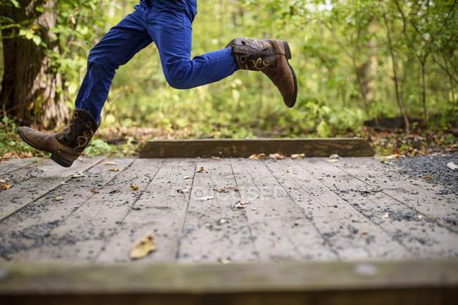 Imagem cortada de Boy correndo através de uma pequena ponte pedonal — Fotografia de Stock