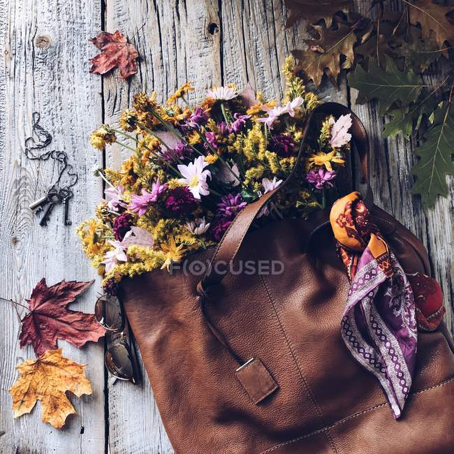 Fall flowers in a brown leather bag — Stock Photo