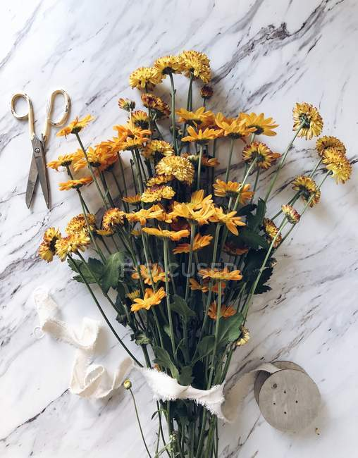 Orange chrysanthemums, scissors and ribbon on a marble table — Stock Photo