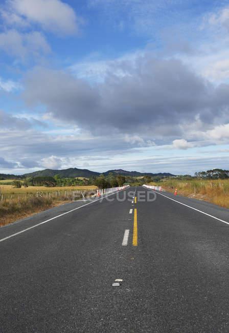Порожній пряма дорога веде до гори, Нова Зеландія — стокове фото