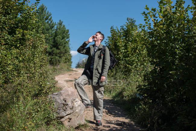 Caminante de pie en un sendero hablando en su teléfono móvil, Bosnia y Herzegovina - foto de stock