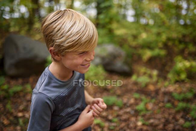 Sonriente niño de pie en el bosque a principios de otoño, Estados Unidos - foto de stock