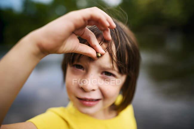 Портрет девушки, держащей миниатюрную оболочку на лбу, притворяющейся единорогом — стоковое фото