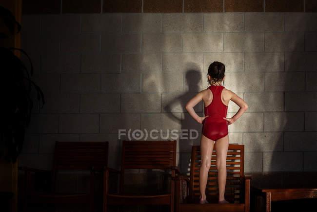 Menina em um traje de natação fazendo sombras contra uma parede — Fotografia de Stock