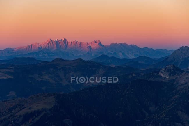 Cordillera de los Alpes austríacos sobre Gastein, Salzburgo iluminada por la luz roja del sol naciente . - foto de stock
