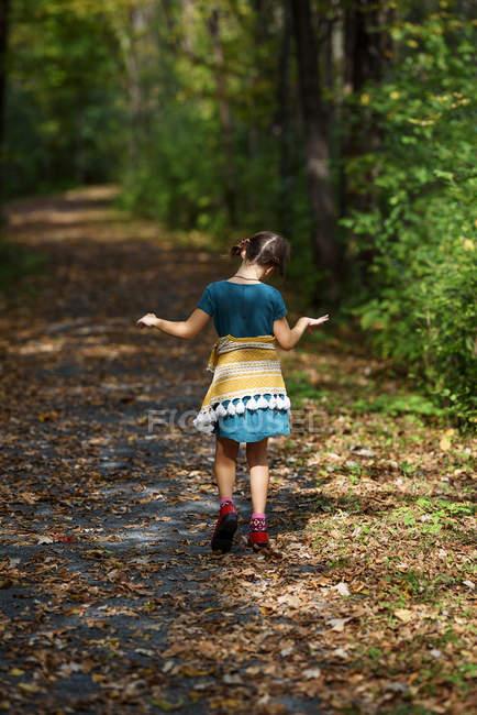 Fille marchant le long d'un sentier au début de l'automne, États-Unis — Photo de stock
