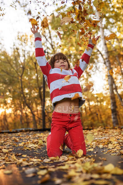 Boy kneeling on a trampoline throwing autumn leaves in the air, United States — Stock Photo