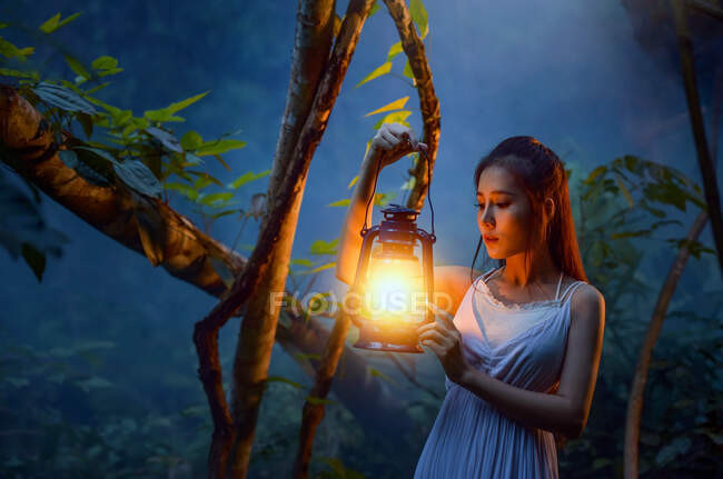Woman standing in forest holding a lantern, Thailand — Stock Photo