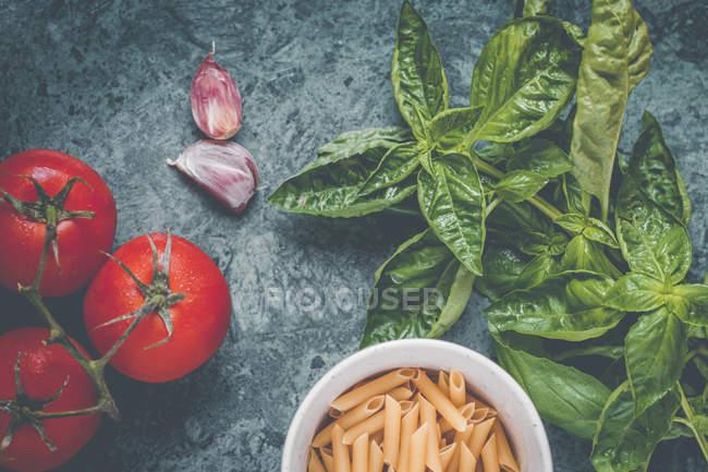 Свежий базилик с макаронами, помидорами и чесноком — стоковое фото