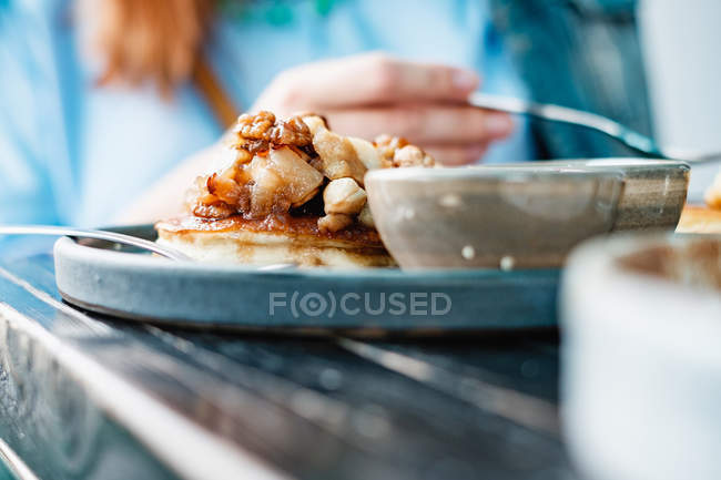Woman eating Pancakes with nuts and honey — Photo de stock