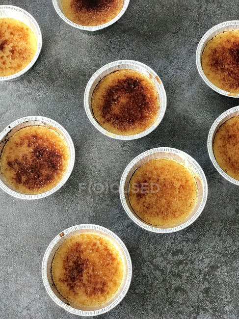 Silver foil ramekins with creme brulee, elevated view — Stock Photo