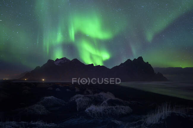Luces boreales sobre el paisaje montañoso de Vestrahorn, Península de Stokksnes, Islandia - foto de stock