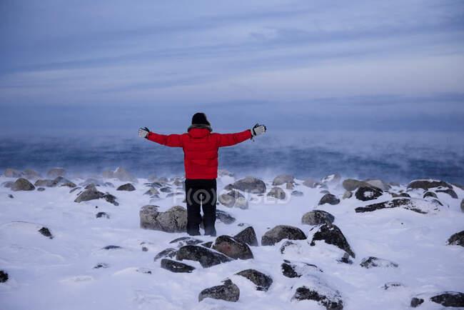 Rückansicht eines Mannes, der im Winter mit ausgestreckten Armen an der Barentssee steht, Murmansk, Russland — Stockfoto