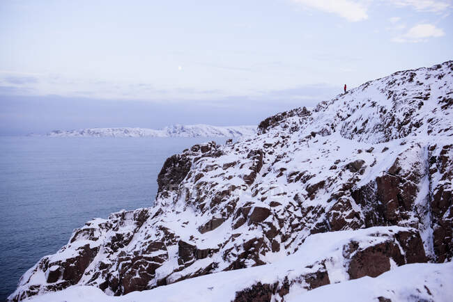 Mann steht im Winter auf einer Klippe an der Barentssee, Murmansk, Russland — Stockfoto