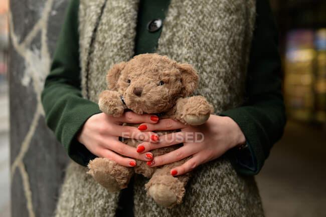 Primo piano di una donna in piedi all'aperto con in braccio un orsacchiotto — Foto stock