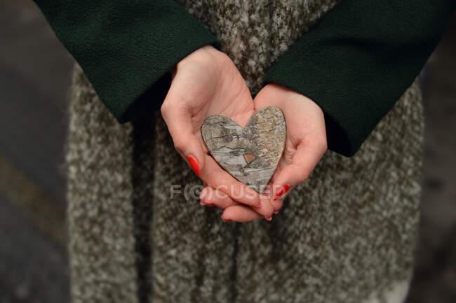 Mani femminili che tengono una decorazione a forma di cuore — Foto stock