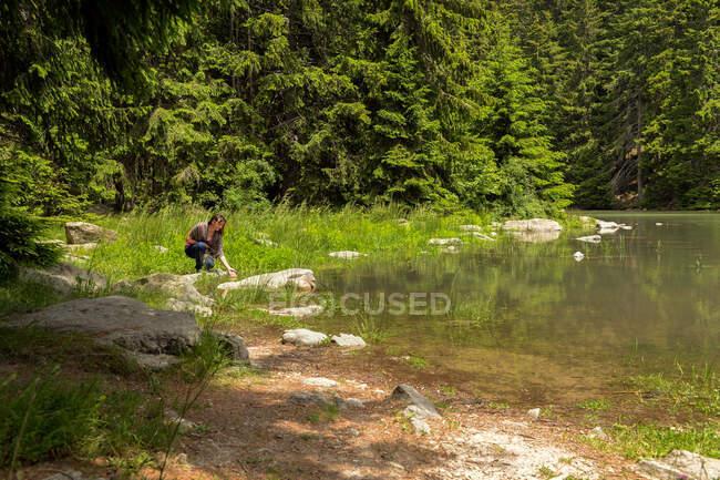 Donna accovacciata su un lago alberato in estate, Bulgaria — Foto stock
