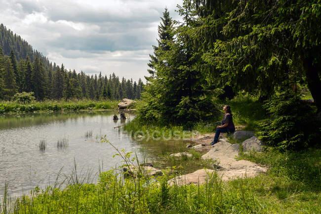Donna seduta su un lago alberato in estate, Bulgaria — Foto stock